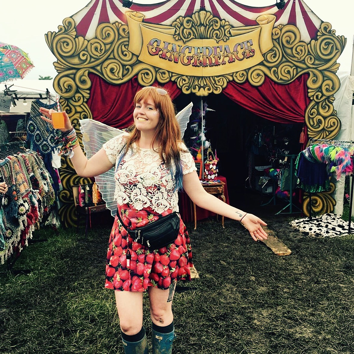 Jessi at Glastonbury festival in front of Gingerface festival stall in strawberry dress