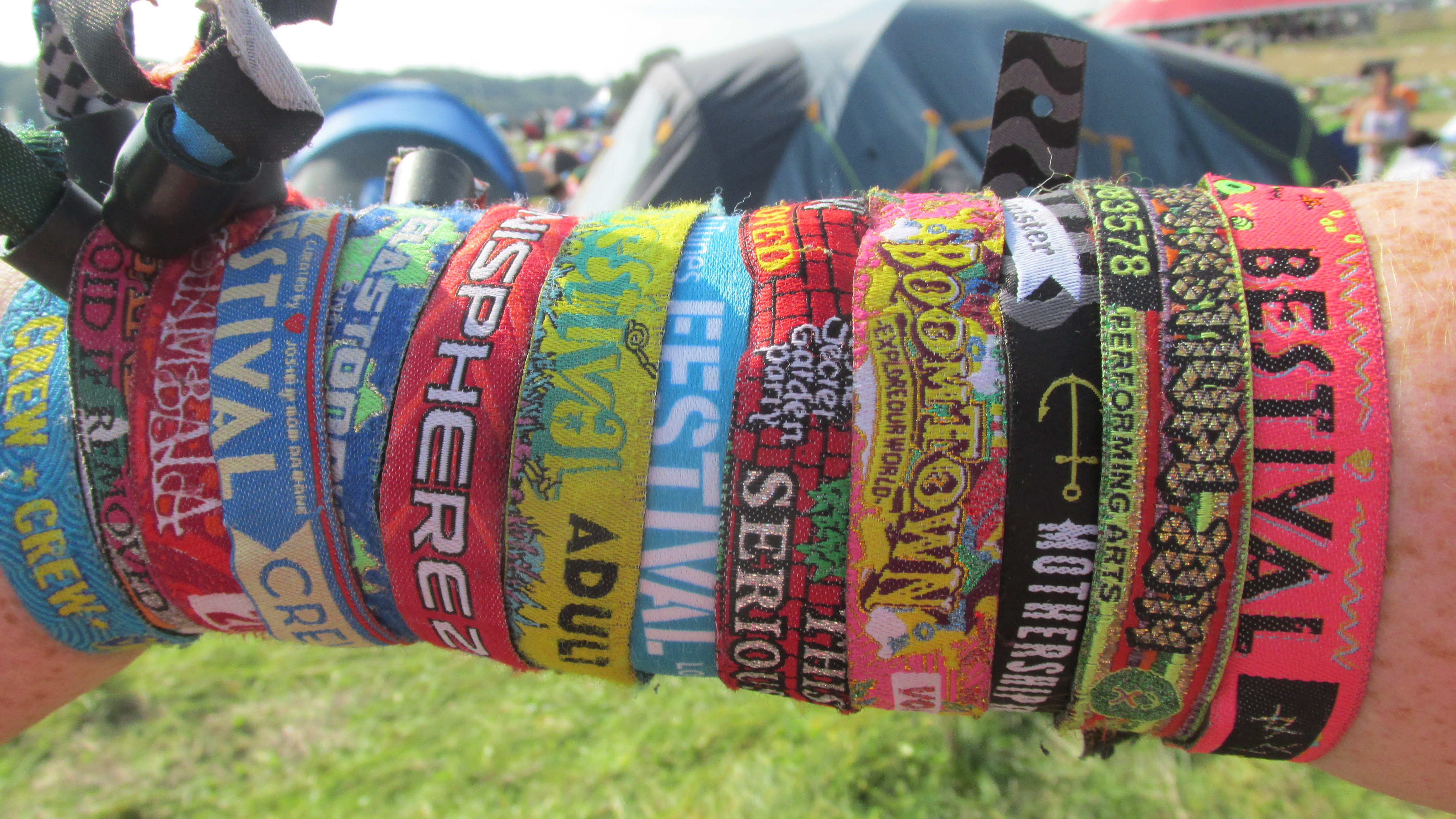 Arm with lots of multi coloured festival wristbands all over Bestival Glastonbury Boomtown Fair Sonisphere