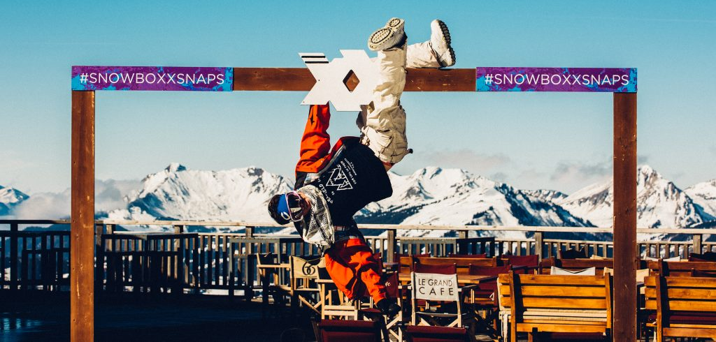 Snowboarder dude hanging from Snowboxx frame posing in front of the mountain range
