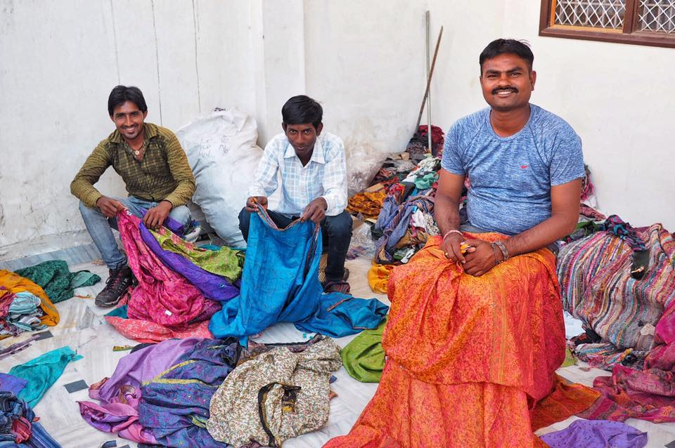 Dulcie's Feathers tailors in Pushkar, India creating the jumpsuits and kimonos from recycled saris. Three tailors sat smiling for the camera.