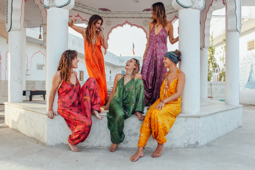 Five girls in beautiful coloured jumpsuits made from saris on a plinth with columns. Festival wear from Dulcie's Feathers