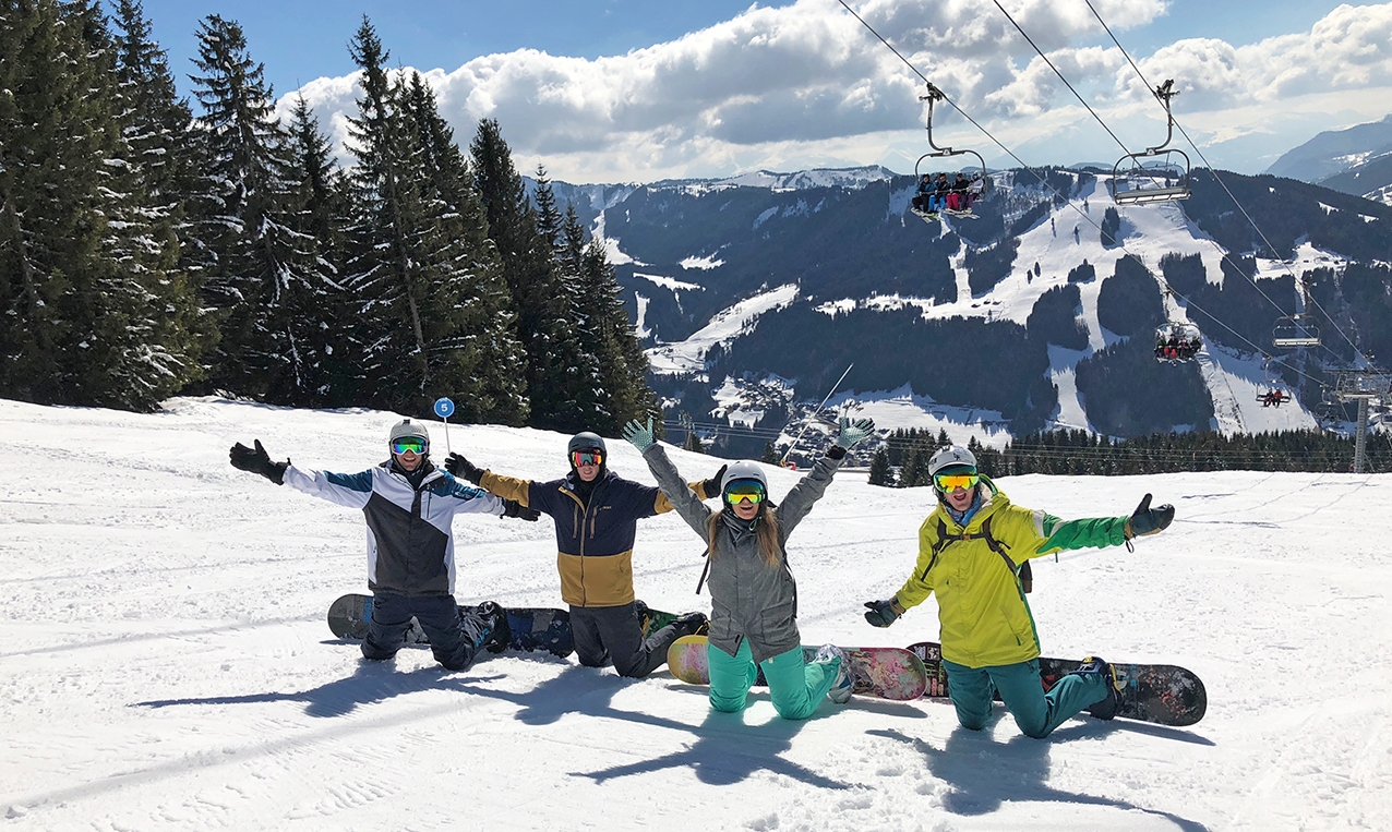 Stafford, Andy, Ell and Harriet, all the snowboarders, posing on piste on their knees with arms in the air