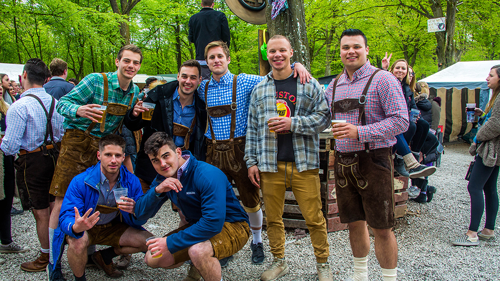 Lads with beers in the Stoke Travel Springfest campsite dressed in lederhosen and posing for the camera
