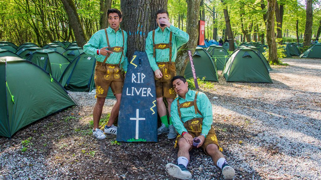 Guys in green lederhosen posing next to a fake gravestone that says RIP Liver on it in the Springfest camp site
