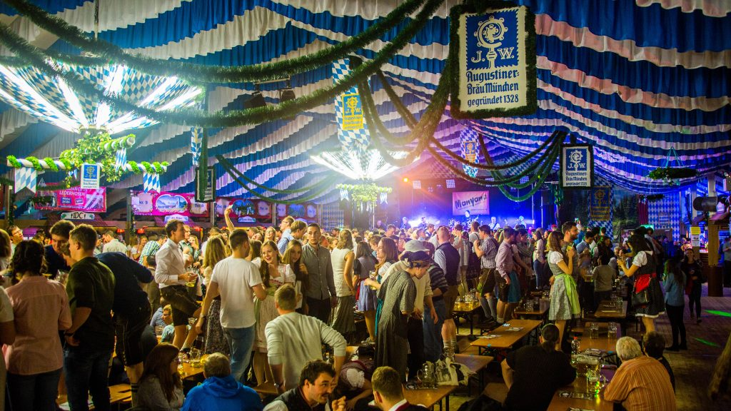 The Springfest festival hall bierfest in Munich - people standing on tables and dancing with steins