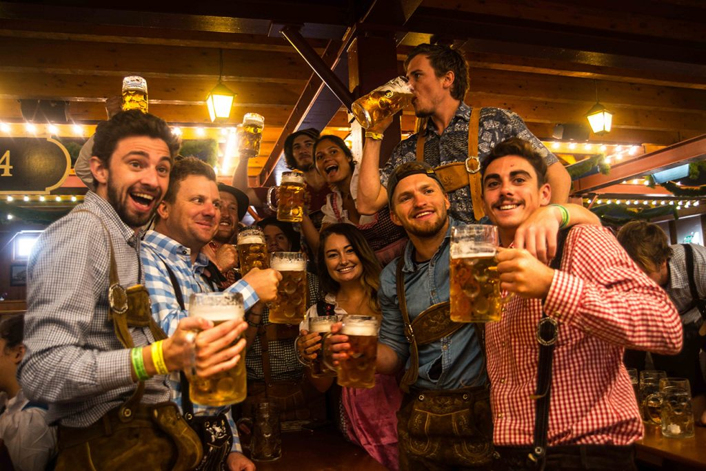 Bailey's friends all dressed the part in the wooden festival hall with steins of beer in hand cheers - ing to the camera