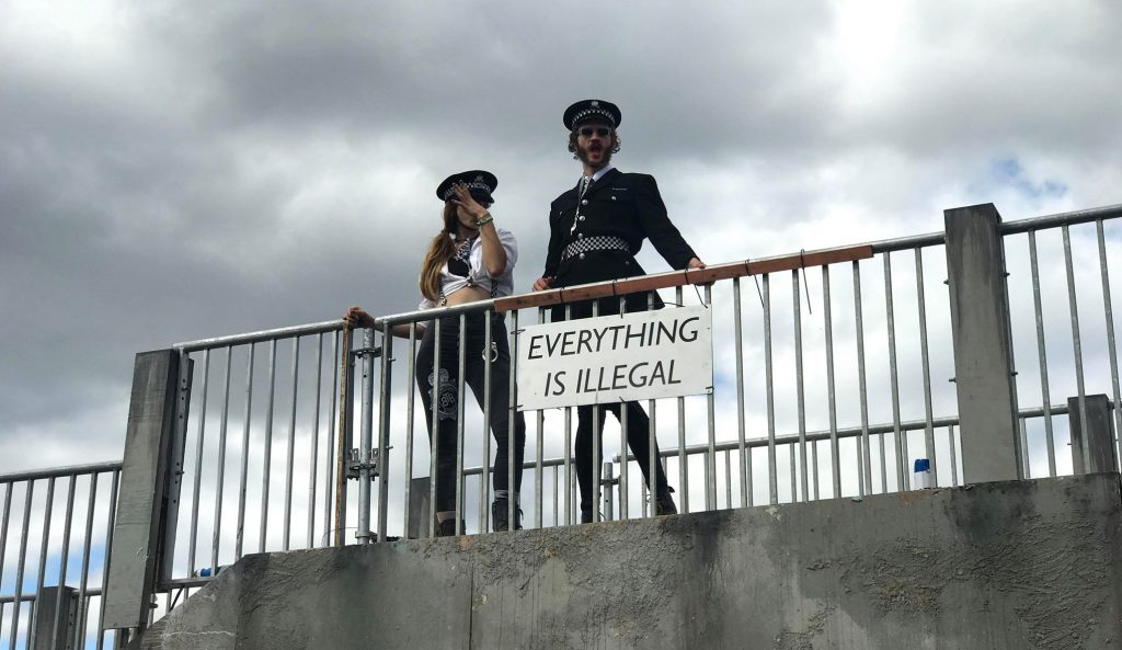 "The Boomtown Bobbies standing up on a building overlooking the Town Centre with a sign that says ""Everything Is Illegal"""