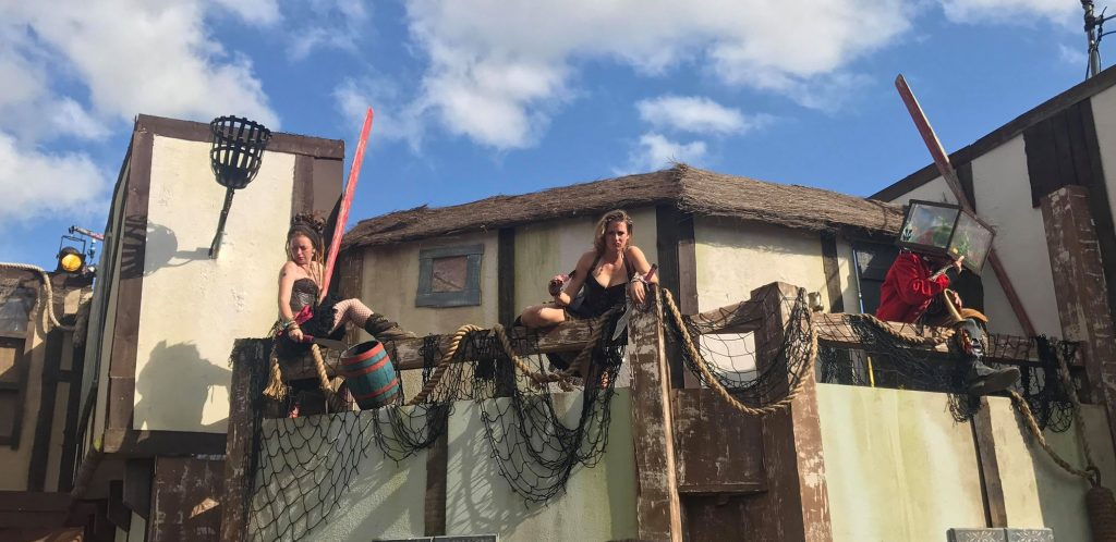 Pirate wenches of Oldtown dangling from rooftops leering at passers by at Boomtown Fair
