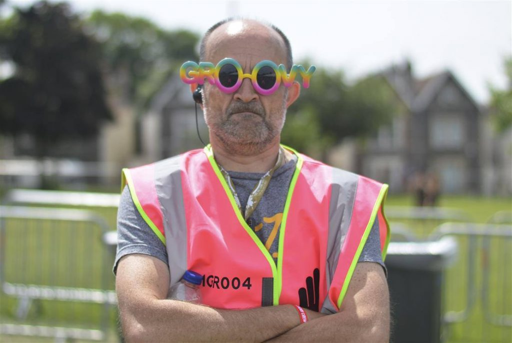"Manager Jon in his neon tabard wearing sunglasses that say ""groovy"" with a slightly stern expression!"