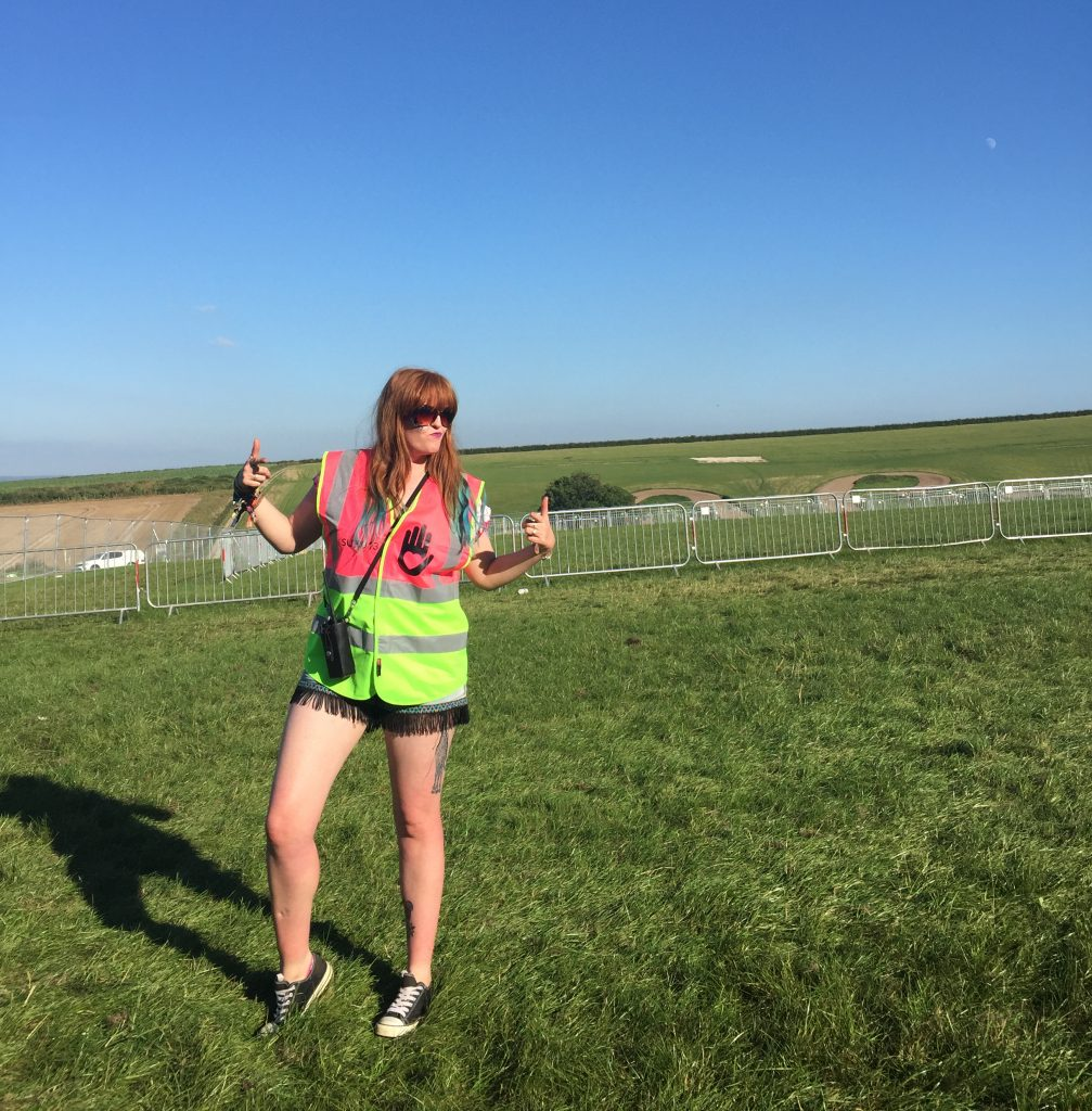 Me in my high vis supervisor tabard posing in an empty car park field in the sunshine at Boomtown Fair