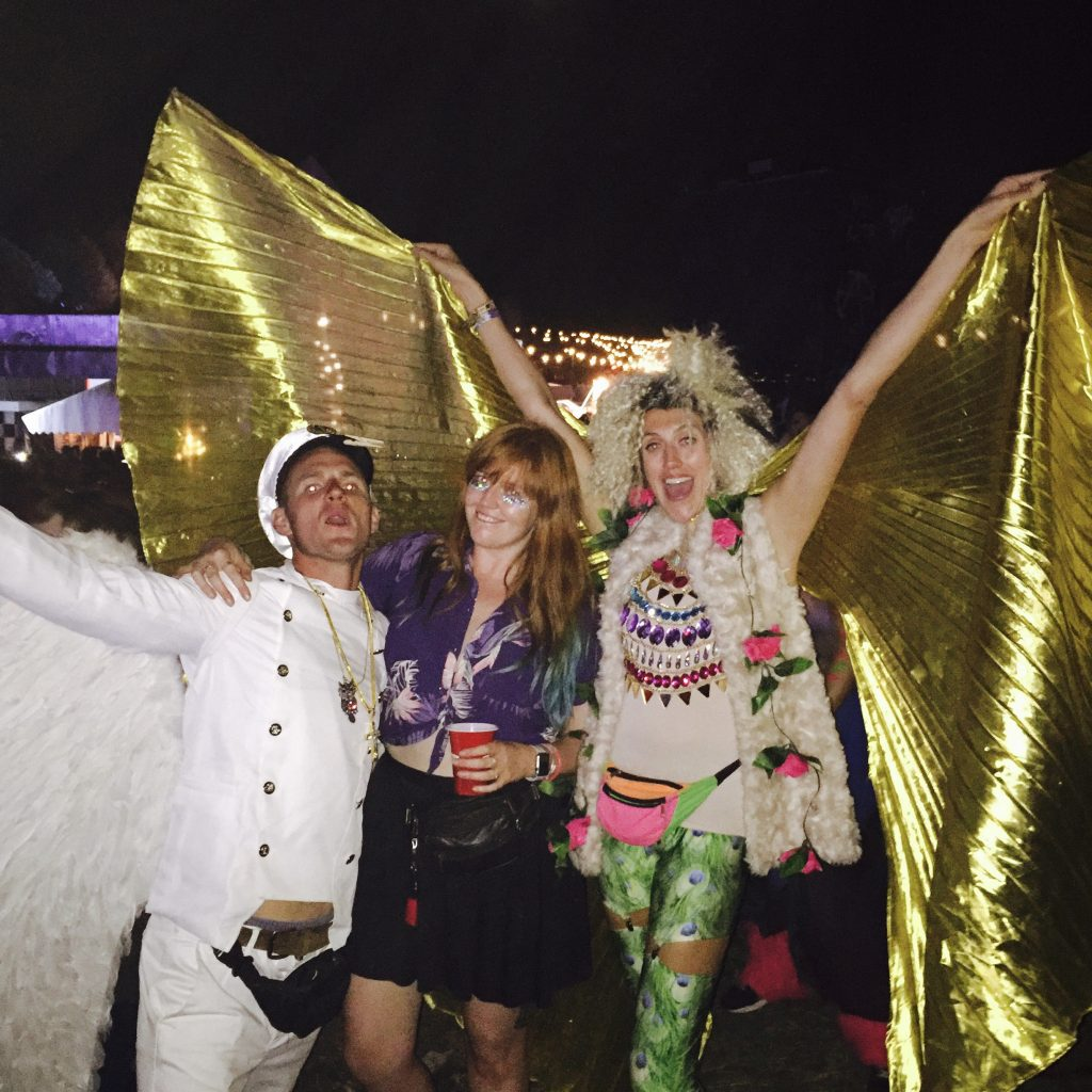 A man in a sailor outfit, me in the middle looking glittery, and a girl with big gold fairy wings pose for a photo at night in downtown Boomtown Fair festival
