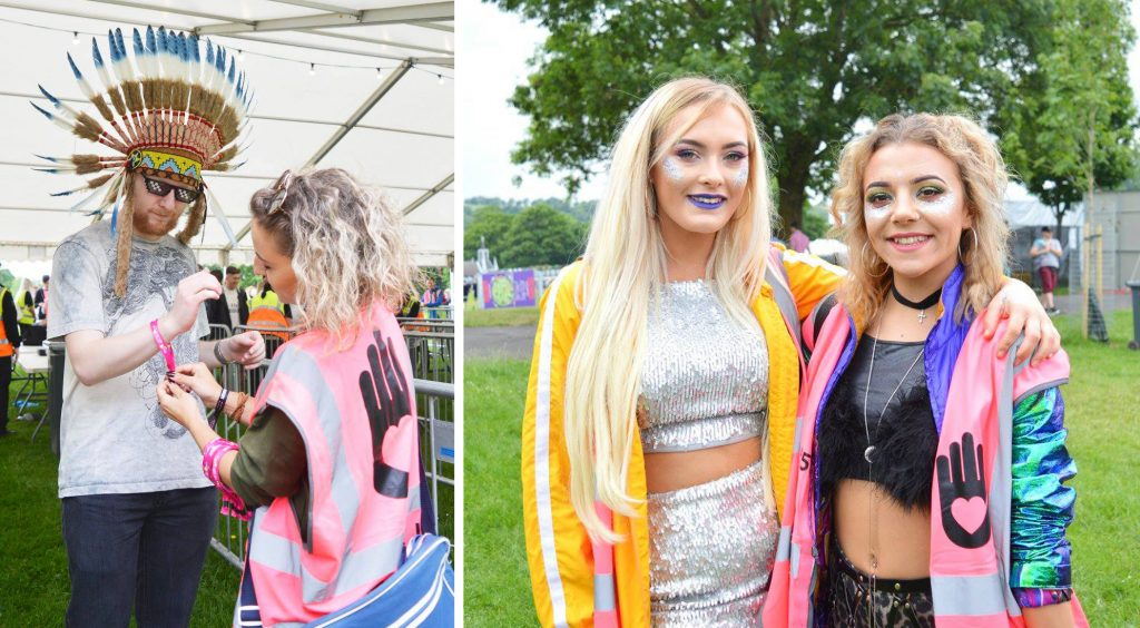 A MyCause UK volunteer putting a wristband on a punter wearing a great headpiece, and two glittery festival girls in their tabards smiling at Love Saves The Day festival