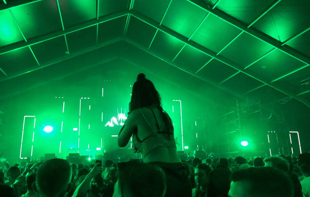 A girl in a glittery bracket is sat on the shoulders of a friend in the crowd at the main stage at We Are Festival surrounded by green light