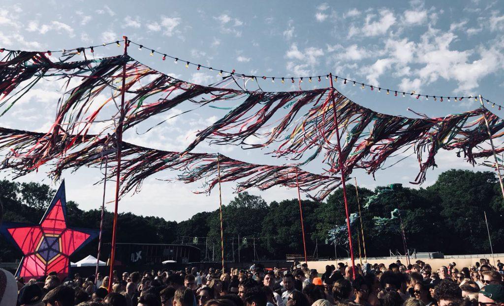 Brightly coloured festival flags and bunting blowing in the wind with a blue sky backdrop above the Common People crowd