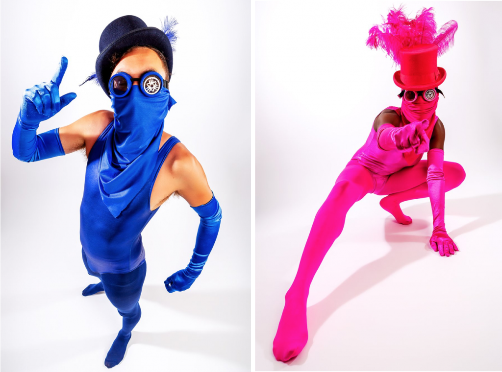 These colourful revolutionaries are wearing scarf masks, goggles, top hats and one piece catsuits. One is in all royal blue, and one in all hot pink.
