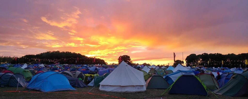 Beautiful orange and pink sunset over the Shambala campsite. Hundreds of tents as far as the eye can see.