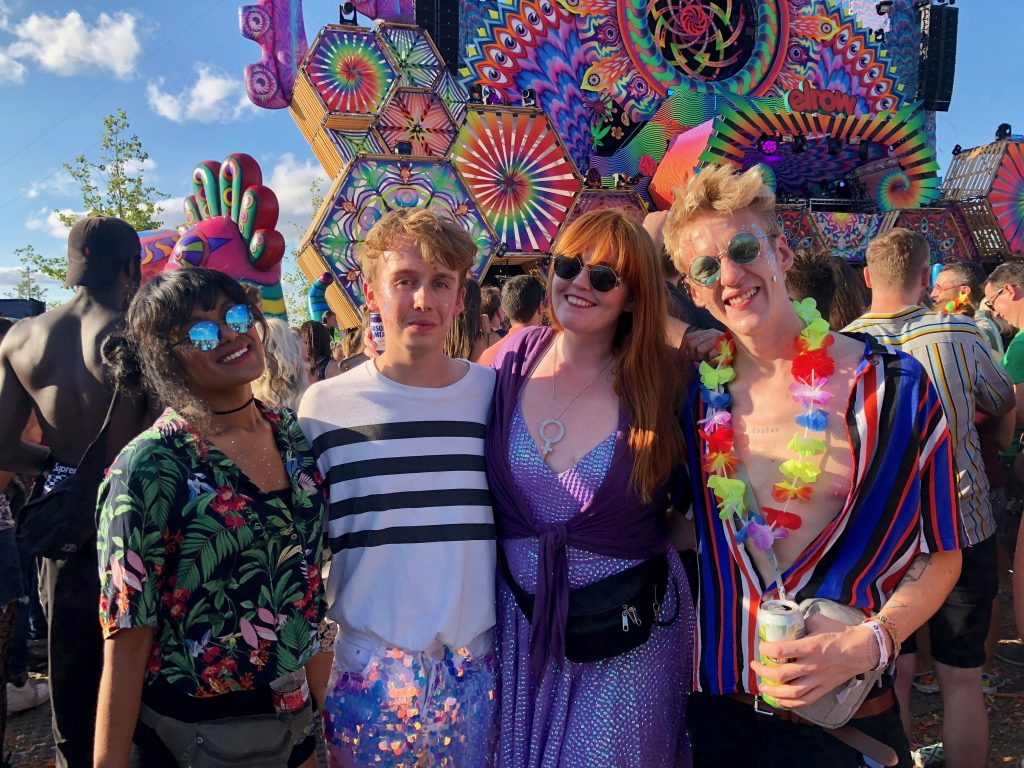 Laurie, Iain, myself and Thom smile for the camera with the cog/hexagon main stage behind us, all squinting from the sunshine from behind sunglasses!