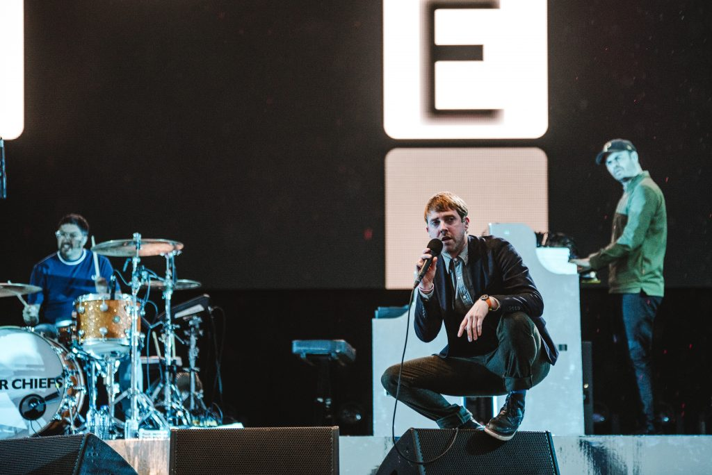 The Kaiser Chiefs on stage at Victorious Festival - Ricky Wilson squats on top of the monitor stage speaker whilst singing
