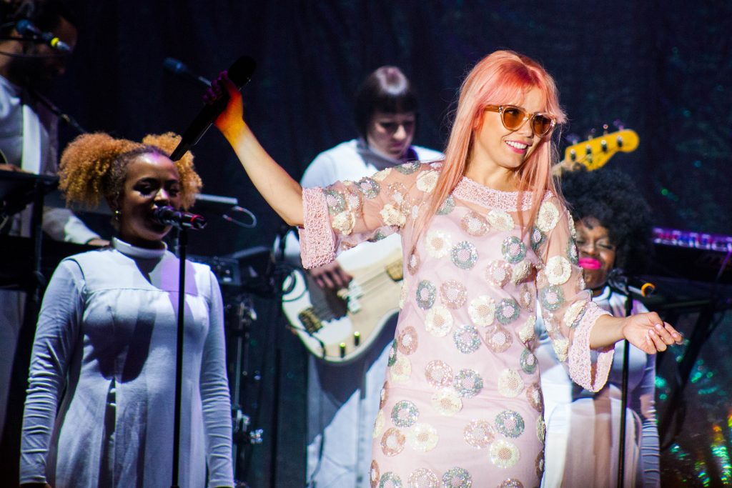 Paloma Faith on stage looking radiant with light pink/peach coloured hair and a pink dress with sequin flowers in front of her all female band on the Victorious main stage