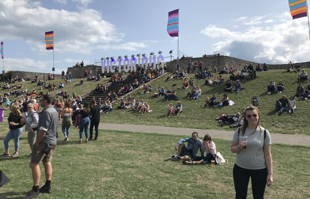 """Harriet poses for a photo in the sunshine of the Victorious Case Stage field, with the """"Victorious"""" sign on the hill behind her and festival flags flying in the breeze"""