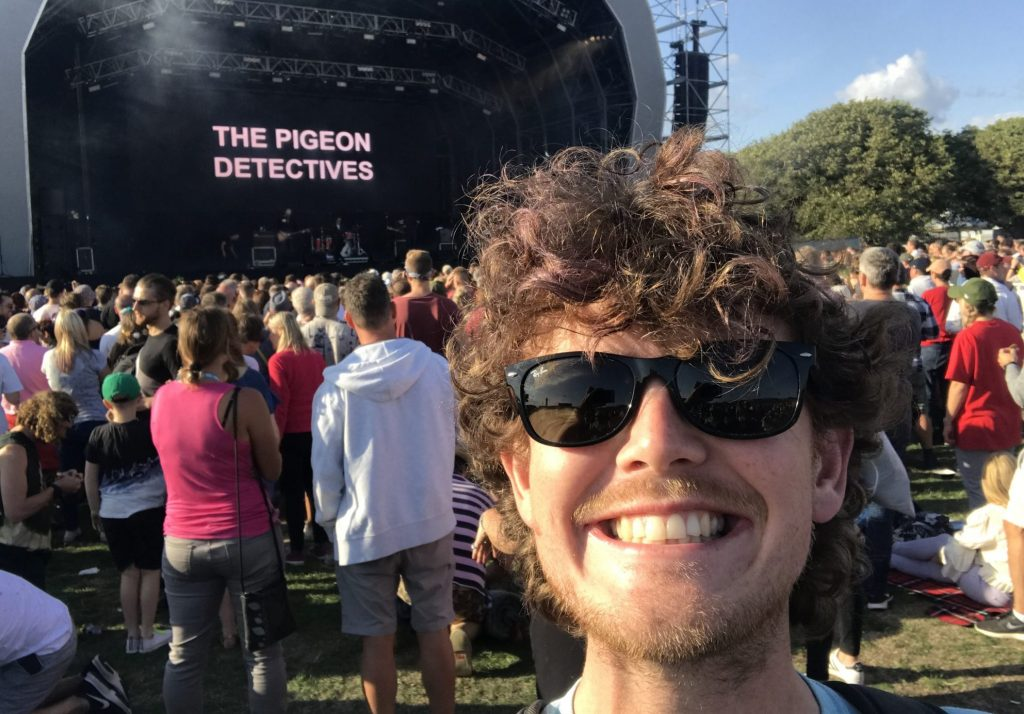 """Stafford with a cheesy grin in front of the stage that has """"The Pigeon Detectives"""" in large letters on the screen"""