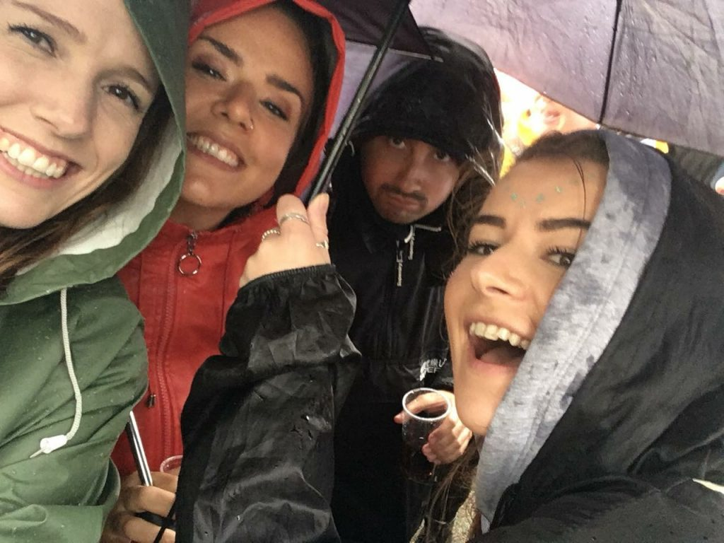 Group selfie of Harriet and friends huddled under an umbrella