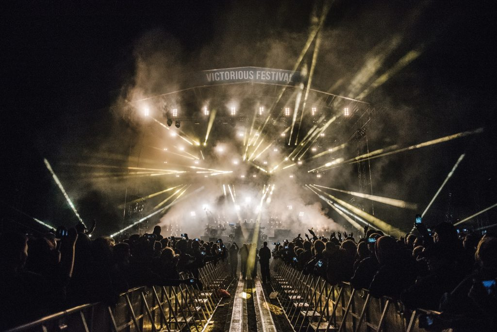 View of the main stage whilst Prodigy perform from the sound desk with lots of white laser lights and fog