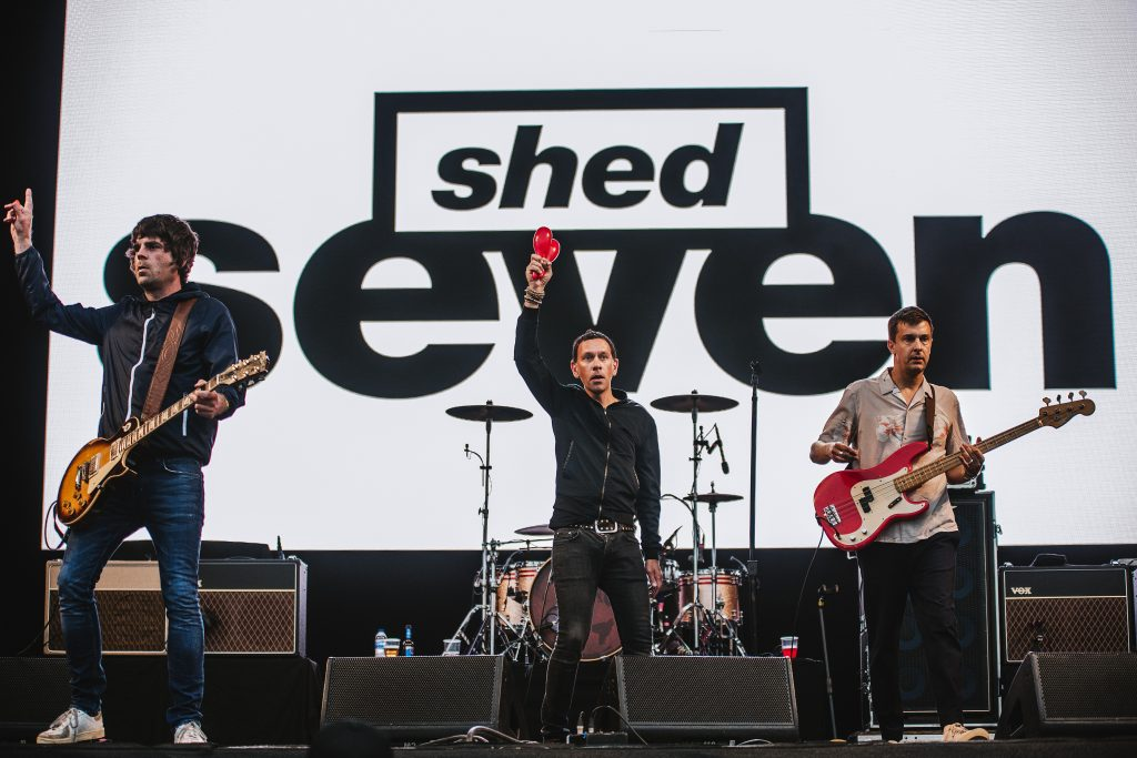 Shed Seven pose with their hands in the air in front of their large logo sign on the main stage
