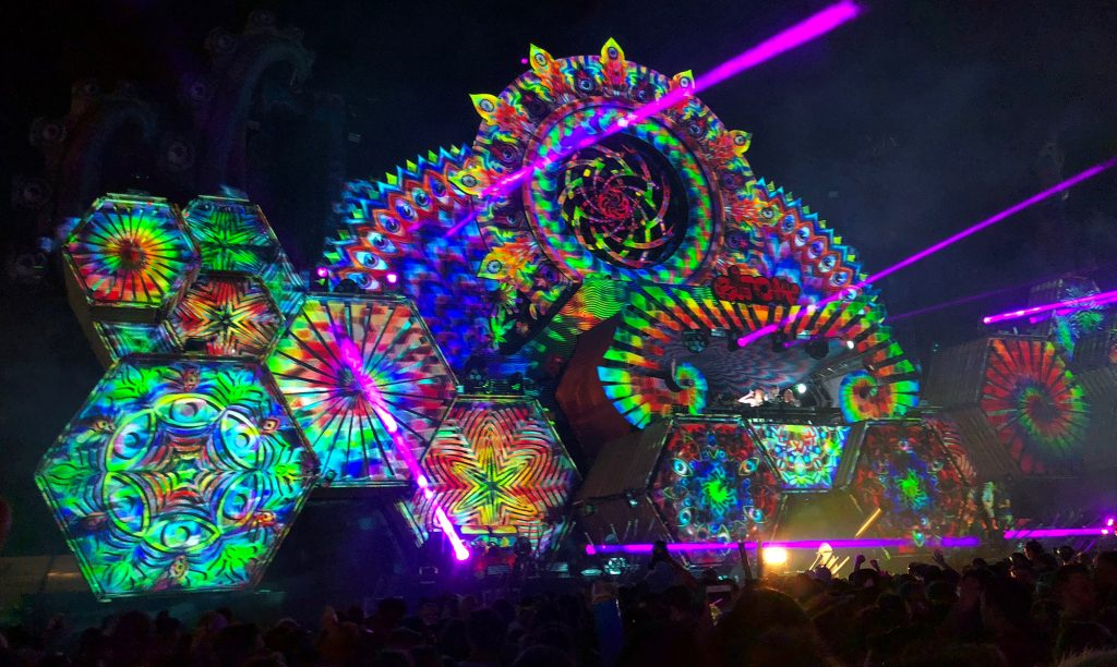 As Fatboy Slim took to the decks, the main stage lit up with projection mapping and became even more colourful! There are pink lasers being beamed over the crowd