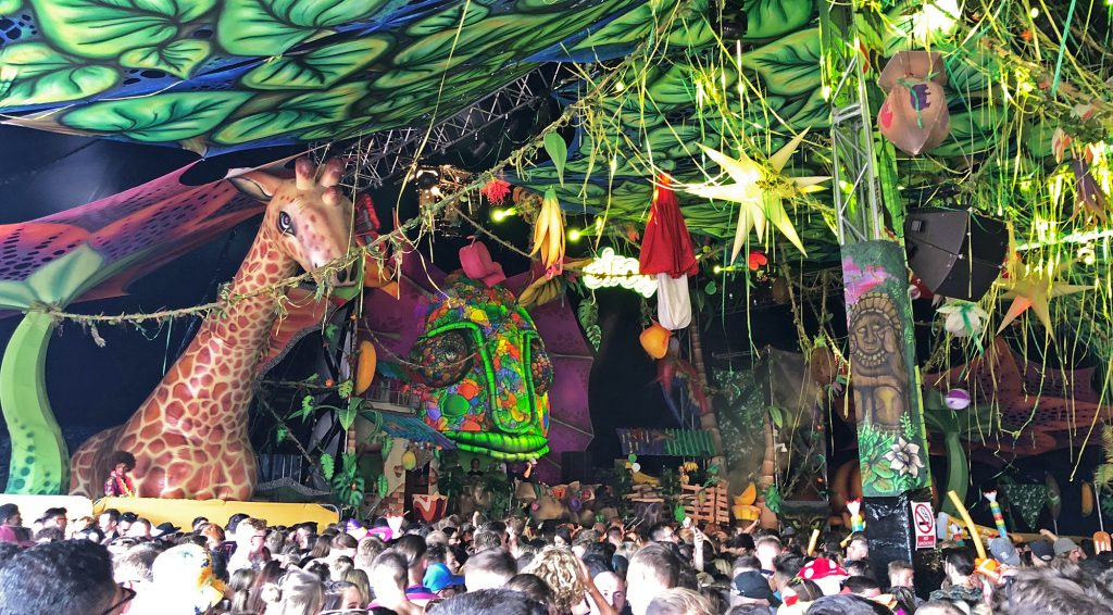 """The inside of """"The Cave"""" big top tent at Elrow Town: the ceiling is patterned with leaves and has streamers cascading down, the stage area has a giant multicoloured neon lizard face looming over it and there's a huge inflatable giraffe peering out over the crowd"""