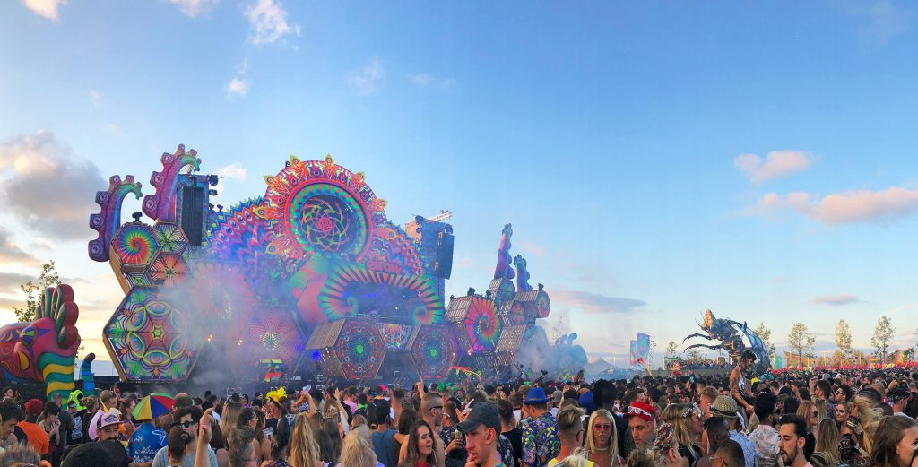 Blue skies look beautiful over the multicoloured, psychadelic main Elrow Town stage with the crowd in front.