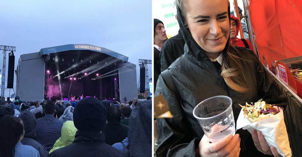 View from the crowd of the Victorious main stage with grey skies overhead, and Harriet looking pleased holding her falafel pitta and a pint