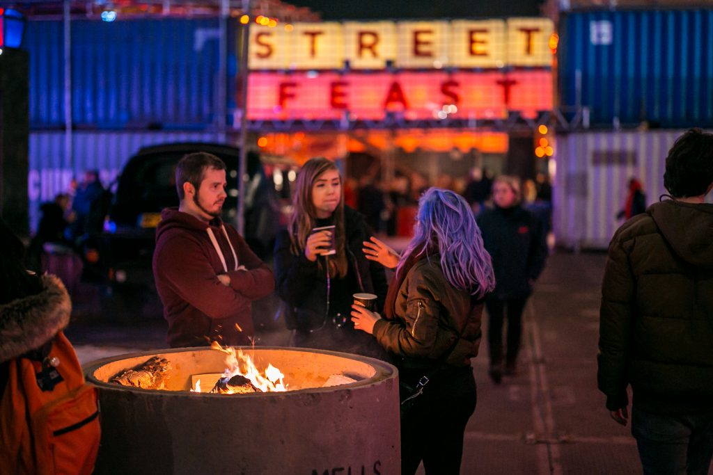 Three friends stood near the front entrance to the Street Feast area which is made from shipping containers. They are holding cups of mulled wine/hot chocolate and are having a conversation.