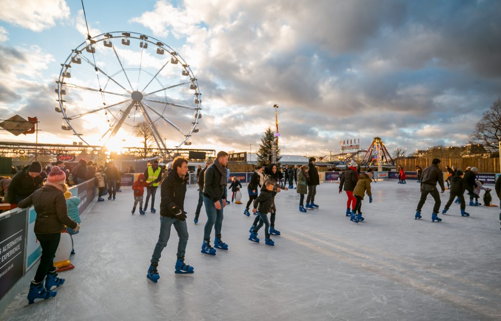 View of the ice rink at Winterville, lots of people ice skating beneath blue but cloudy skies, with the fairground Big Wheel in the background