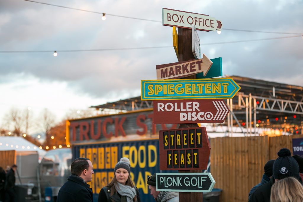 The signpost at Winterville winter festival, showing the direction to the different areas including Spiegeltent, Street Feast, Plonk Golf, the market and more
