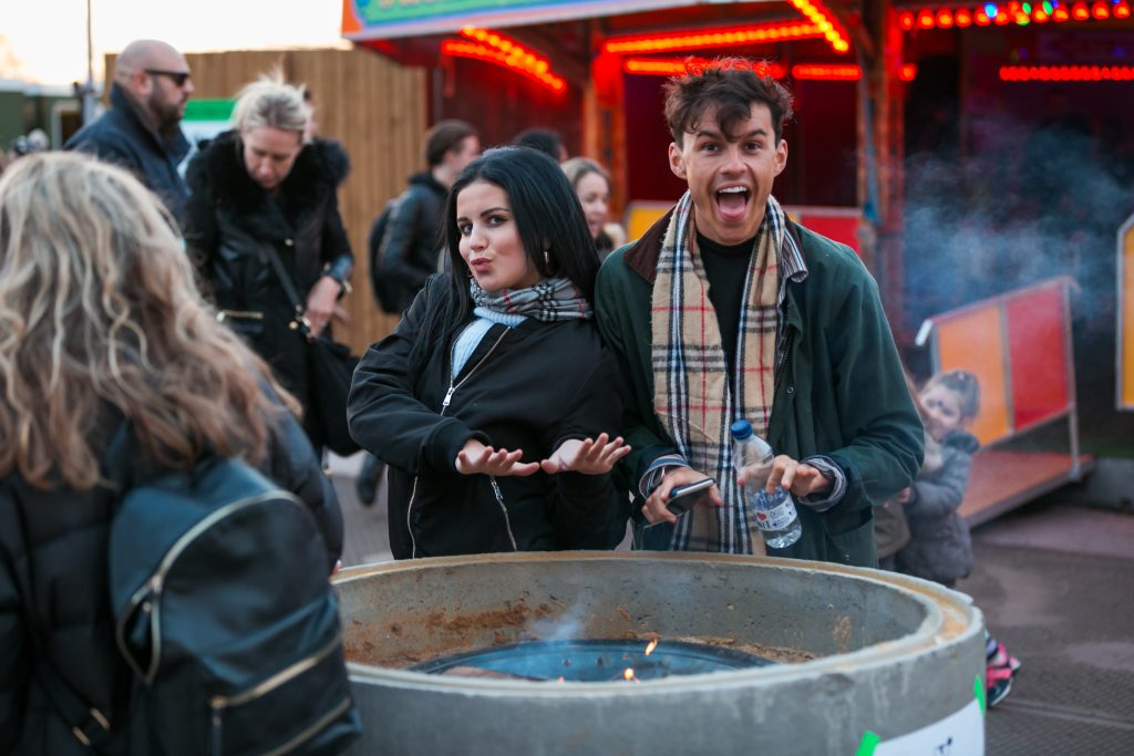 Man and woman stood by a fire pit posing with big smiles at Winterville