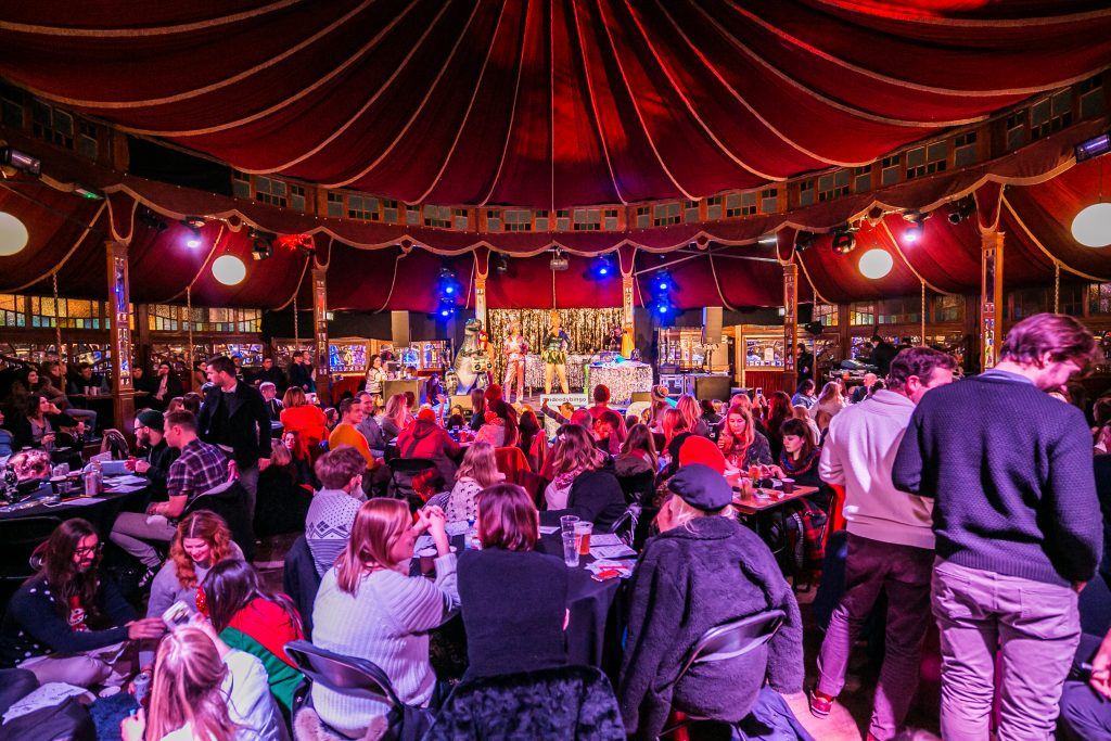 The view looking at the stage of the Spiegeltent, with the middle floor hosting round table of people, and the magnificent circus-style roof showcasing the round tent at Winterville