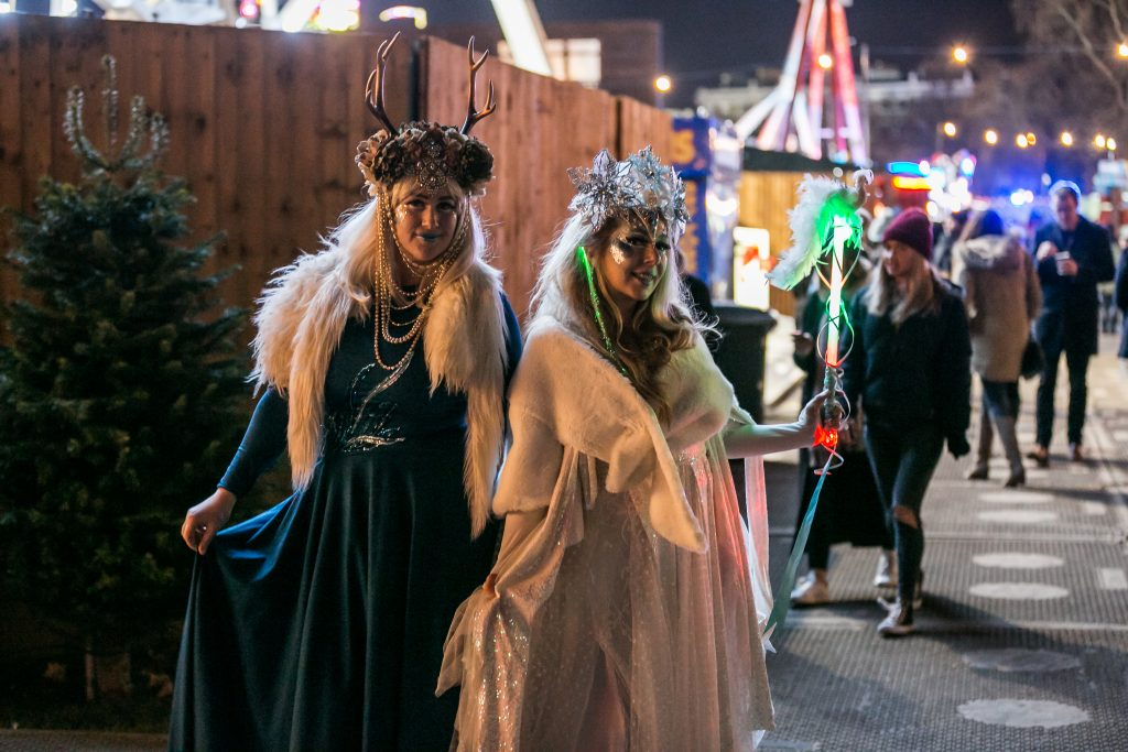 Two ladies dressed as winter fairies/goddesses, wearing velvet dresses, headdresses and fur collars.