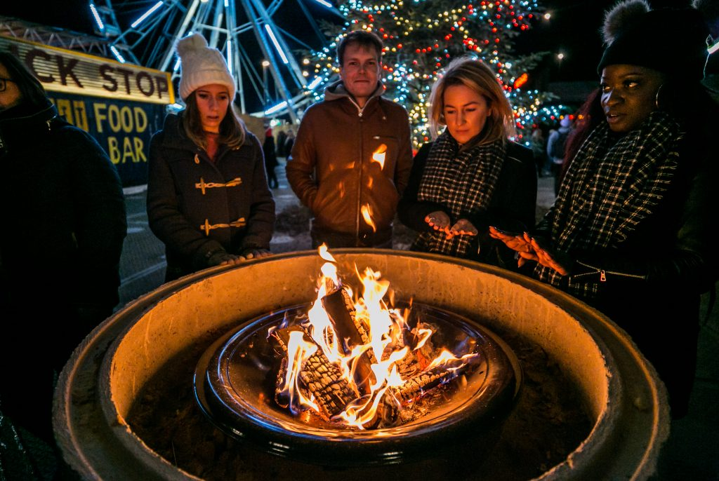Group of 4 people warming their hands on a fire pit, with the Winterville Christmas tree and big wheel in the background